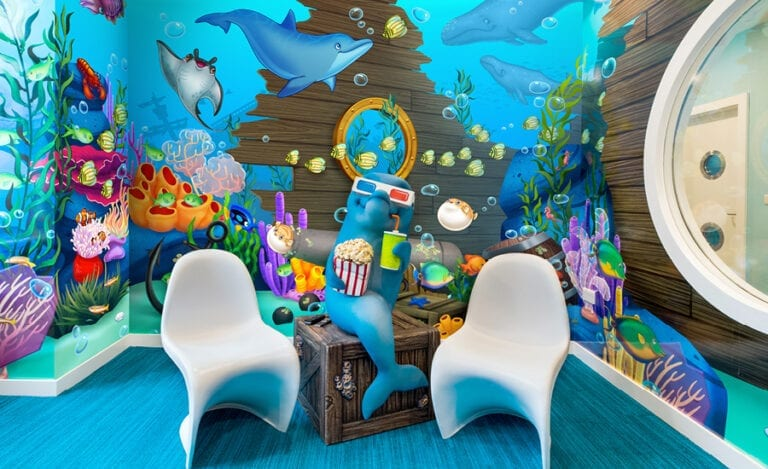 3d dolphin character with popcorn, drink, and 3d glasses in underwater themed kids theater
