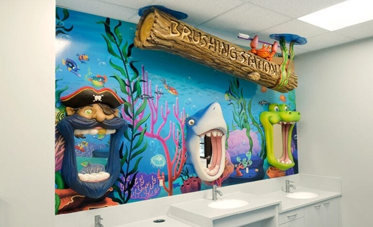 Brushing station with a ceiling hung log sign, brushing mirrors and a mural backdrop