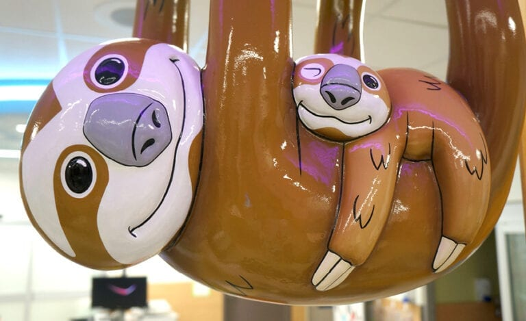 Close up of a stylized, sculpted sloth mother and sloth baby