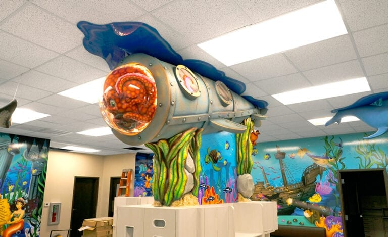 Custom foam carved submarine mounted to the ceiling of a dental treatment bay with octopus character inside.