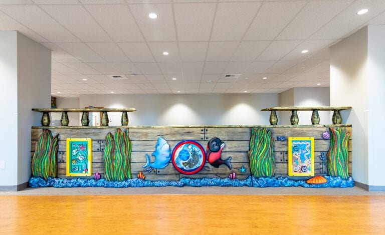 custom wall divider with play panels separating a medical office waiting room kids section sculpted to look like a shipwreck with coral and fish details