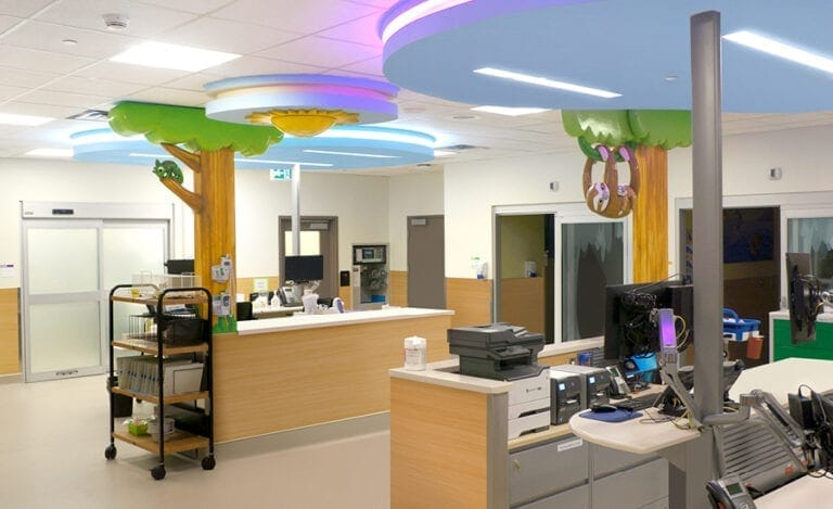 Custom sculpted trees with sloth and chameleon characters in a nurses station at a hospital