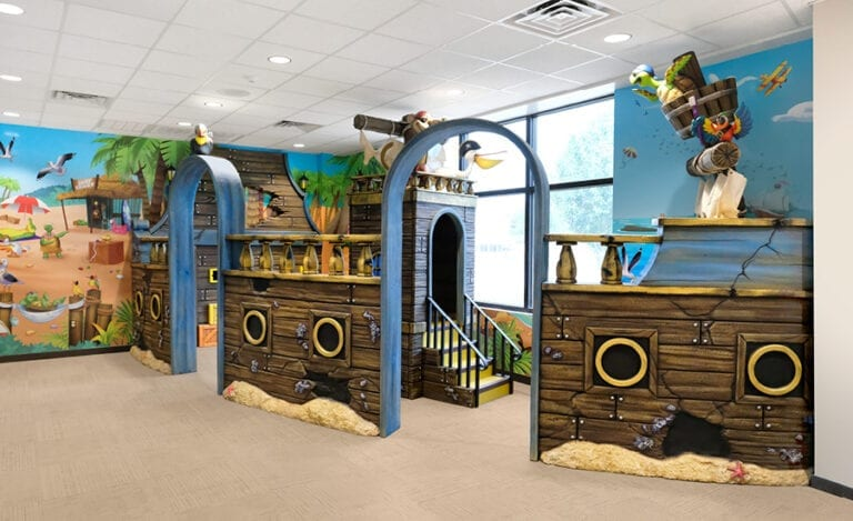 Enclosed kid's play corner in dental office with pirate ship themed walls, sculpted pirate animal characters and yellow slide