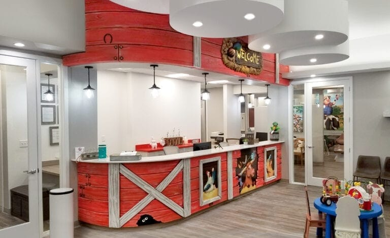 Farm themed reception desk featuring bright red barn inspired cladding and animal portrait murals