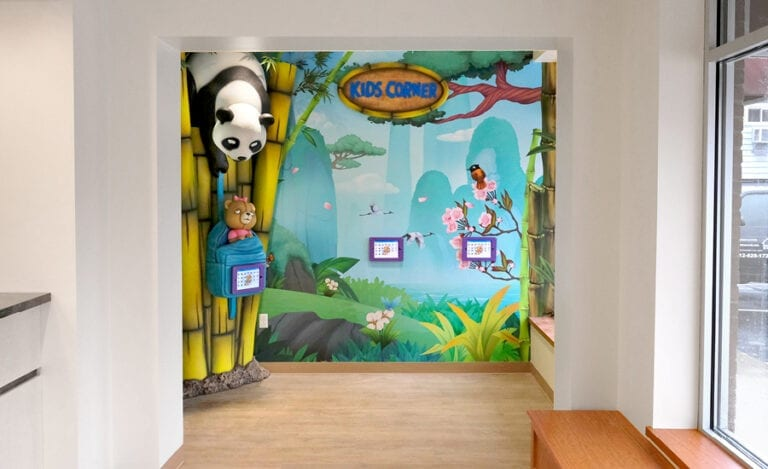 """Kid's playroom with wall mural of an Asian mountain range, game tablets, and bamboo """"kids corner"""" signage"""