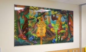 Large I spy graphic with a jungle theme hanging on the wall in a clinic waiting room