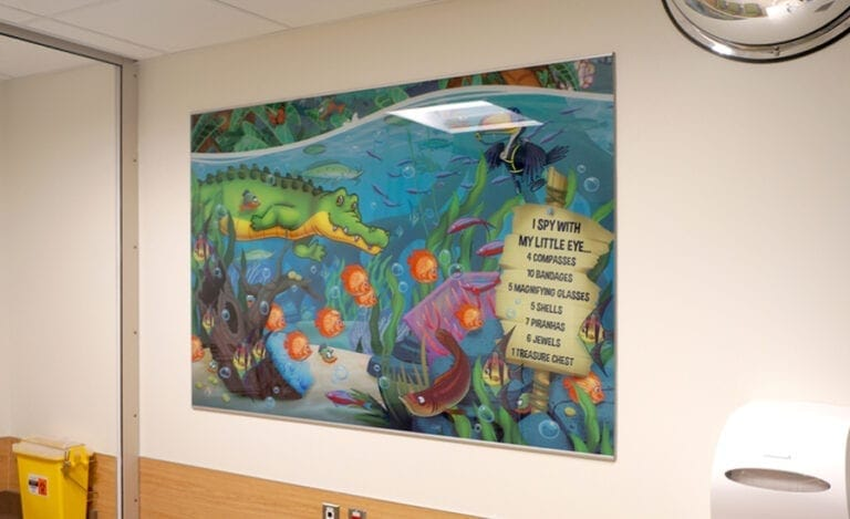 Large I spy graphic with a river theme hanging on the wall in a hospital waiting room