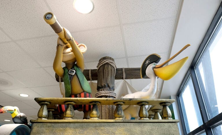 sculpted pirate monkey and pelican looking out from a ship mast in a children's playroom