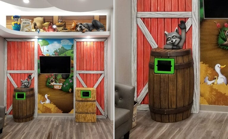 Play corner with barn red door wall cladding, sculpted farm animals and a countryside mural backdrop