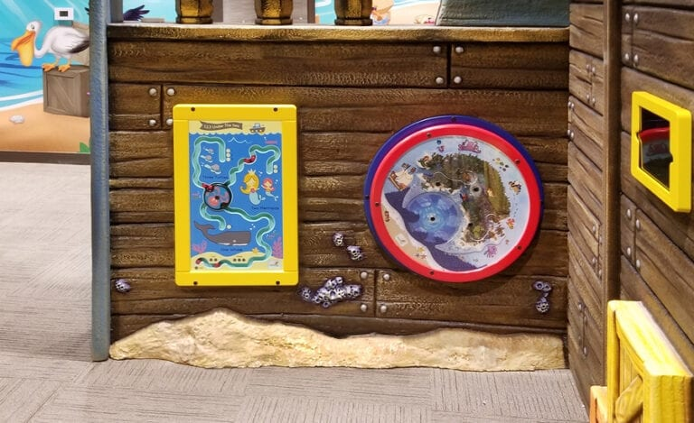 Play panels on a custom pirate ship wall in kids playroom