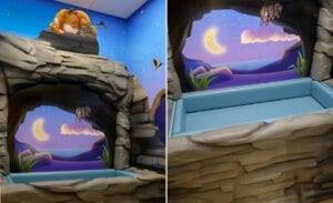 Sculpted cave entrance with an installed toddler bed and a calming nighttime mural backdrop