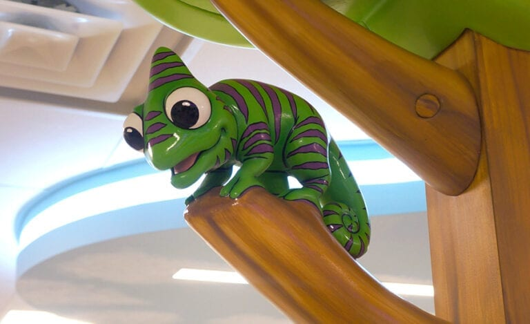 Sculpted green and purple chameleon sitting in a sculpted tree in a hospital