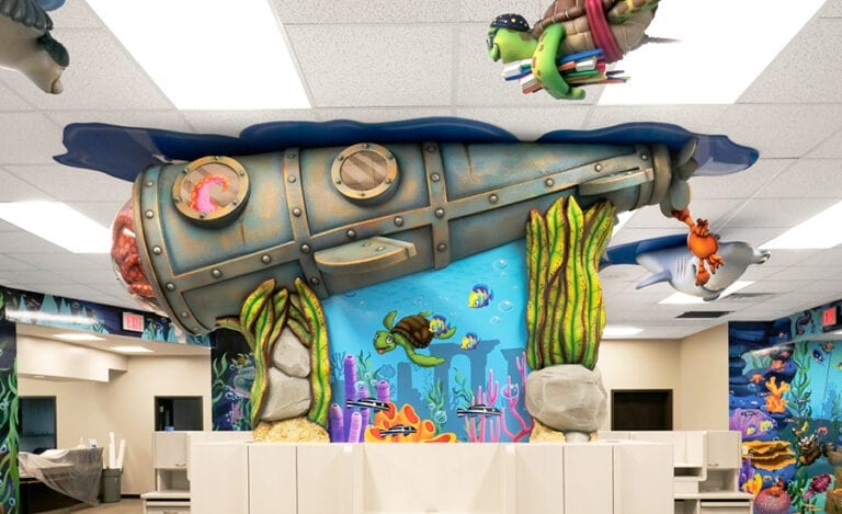 Side profile of a sculpted submarine with custom lighting, an octopus character and seaweed decor with underwater murals