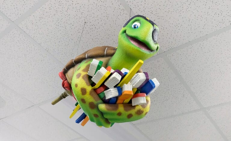Swimming turtle character hanging from ceiling holding a bundle of colorful toothbrushes