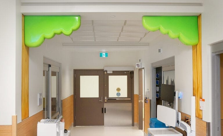 Tree mural with 3D sculpted canopy of leaves in a hospital hallway