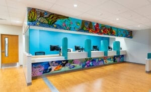 dental reception desk with underwater-themed murals and desk cladding in family-friendly medical clinic