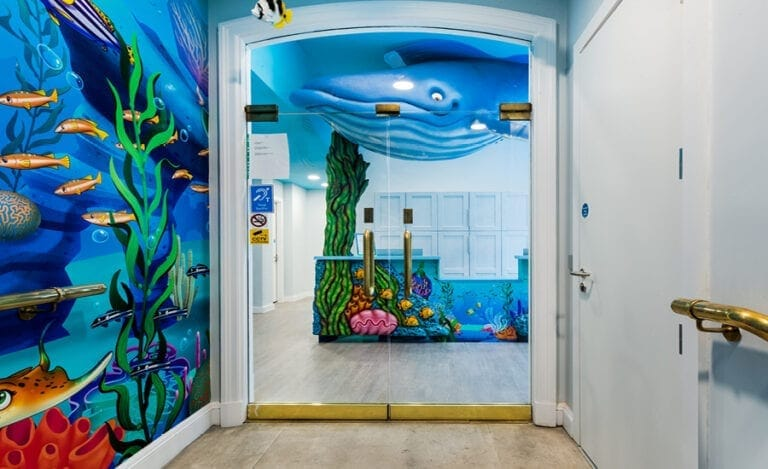 glass doors showing whale sculpture and ocean desk cladding
