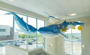 humpback whale sculptures suspended from the ceiling in a stairwell of a themed medical clinic