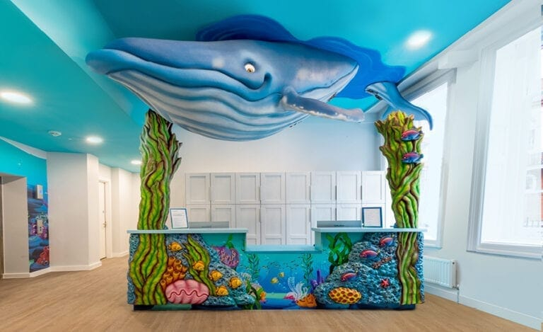 underwater themed reception desk with whale sculpture above, seaweed towers, and coral desk cladding in kids dentist office