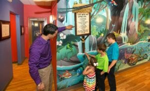 kids playing with i spy game mural filled with jungle animals and landscapes