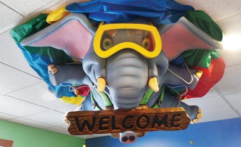 scuba diving elephant ceiling sculpture holding welcome sign for a children's dentistry