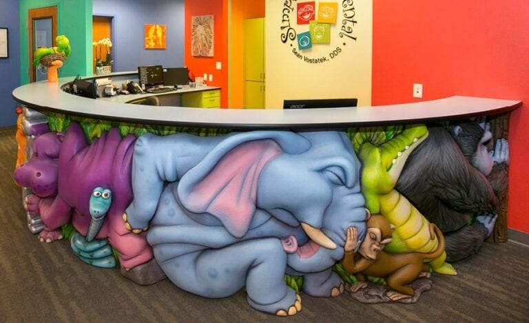 sculpted jungle animals pushing on each other for a silly jungle themed dental reception desk