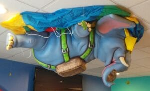 side view of custom ceiling mounted elephant skydiving for a pediatric waiting area