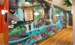 vibrant illustrated wall mural with jungle waterfalls and river animals with an i spy game for a kids dentistry