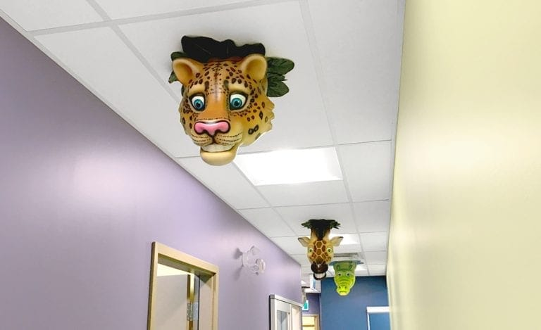 leopard, giraffe, and alligator ceiling characters in a dental office hallway