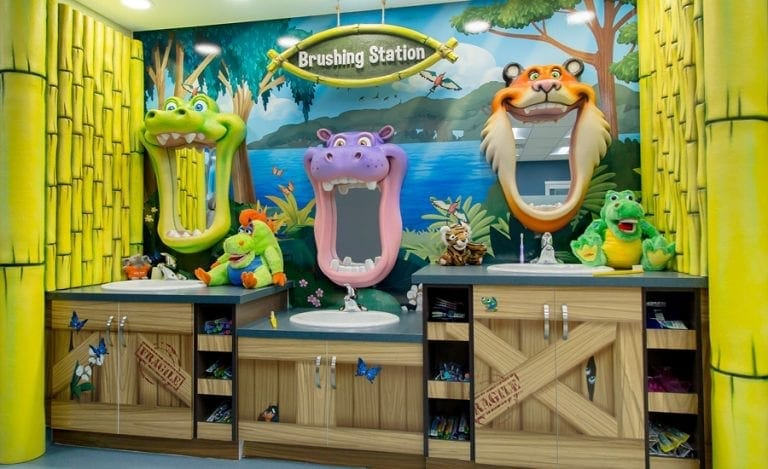 brushing station at a pediatric dental office with jungle character mirrors, hut cladding, and custom murals