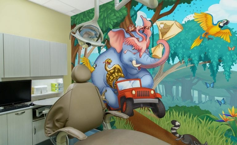 pediatric dental treatment room with a wall mural of an elephant driving a jeep through the jungle