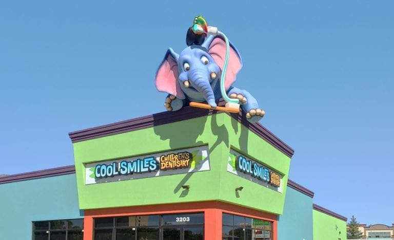 exterior sculpture of an elephant and toucan with a toothbrush on top of a dental office building