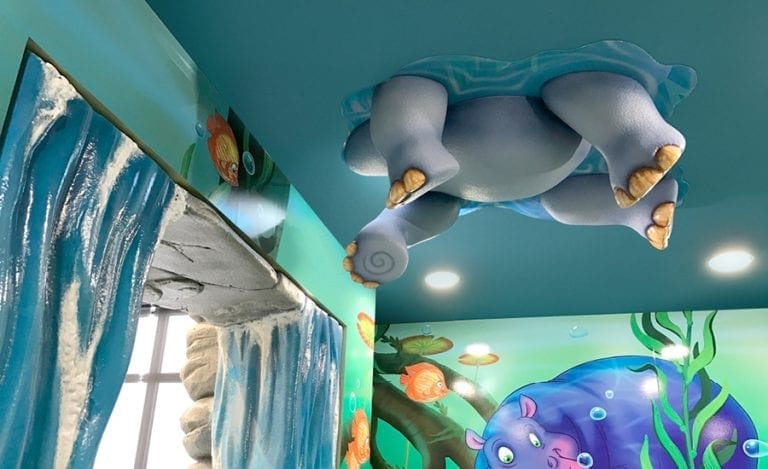 """sculpture of a rhino's legs and stomach """"swimming"""" on the ceiling"""