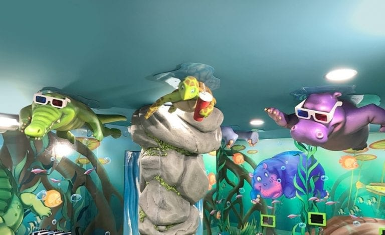 sculpted jungle characters attached to the ceiling wearing 3D glasses in a clinic waiting room