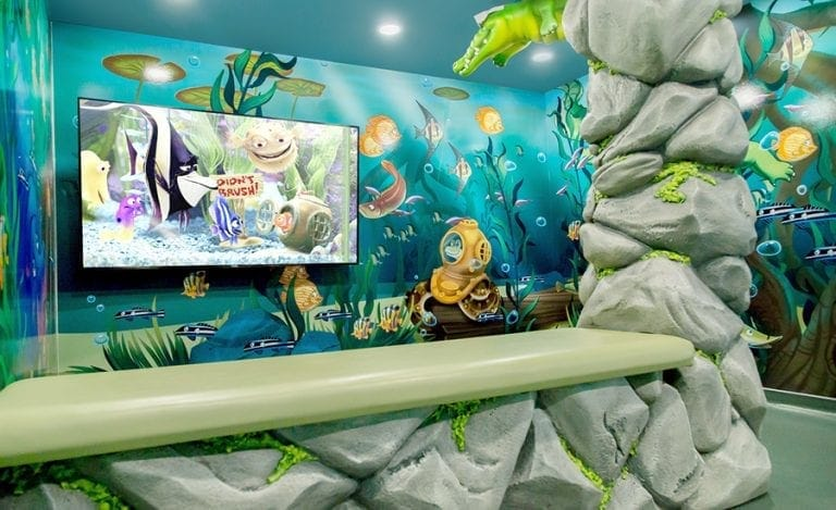 theater room in a pediatric clinic with custom sculpted rock benches, murals, and jungle animal characters