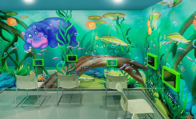 pediatric waiting room with jungle wallpaper and gaming tablets for kids