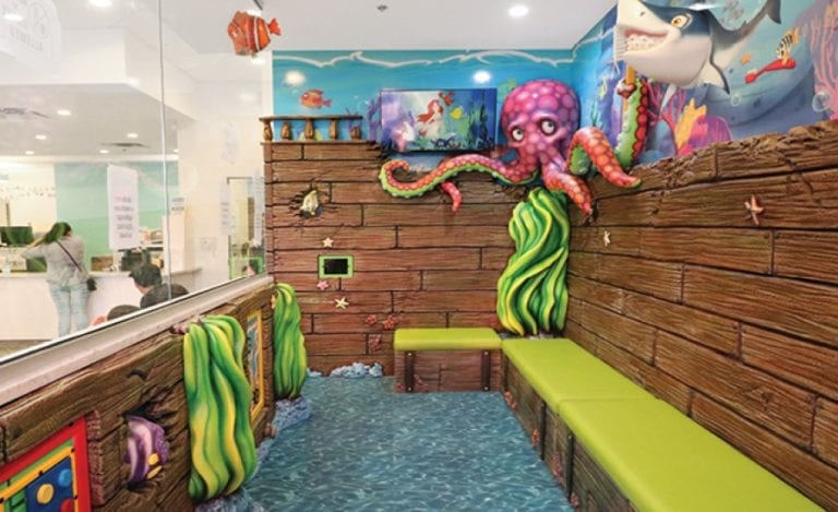 Private play area with KeeBees, tablets, and seating for kids, themed like a sunken ship.