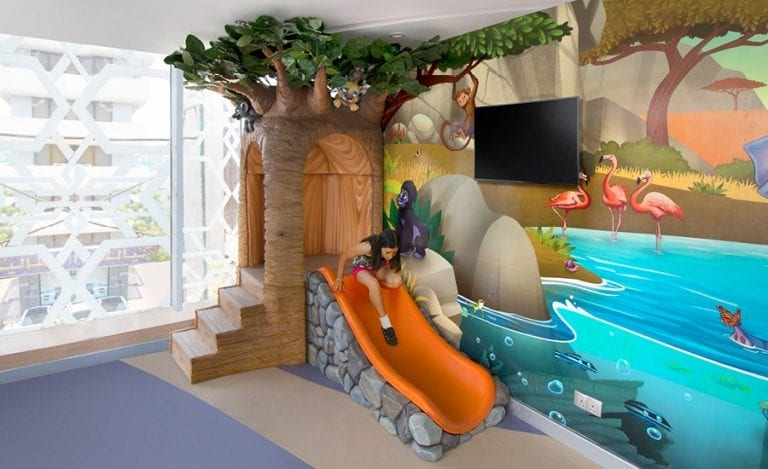 Savanah themed paly corner with a tree shaped slide and safari landscape mural