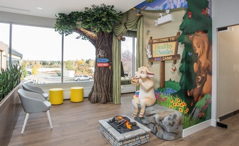 Play area entrance themed like a tent with a goat eating smores by a firepit.