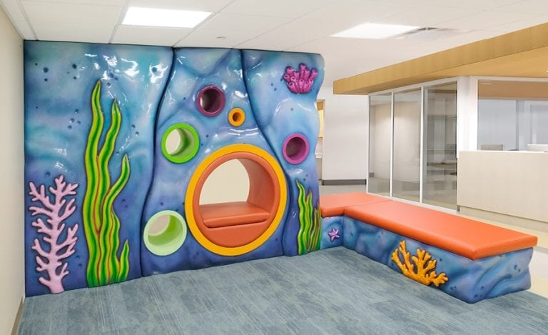 Hospital waiting room with glossy coral seating for kids and adults.