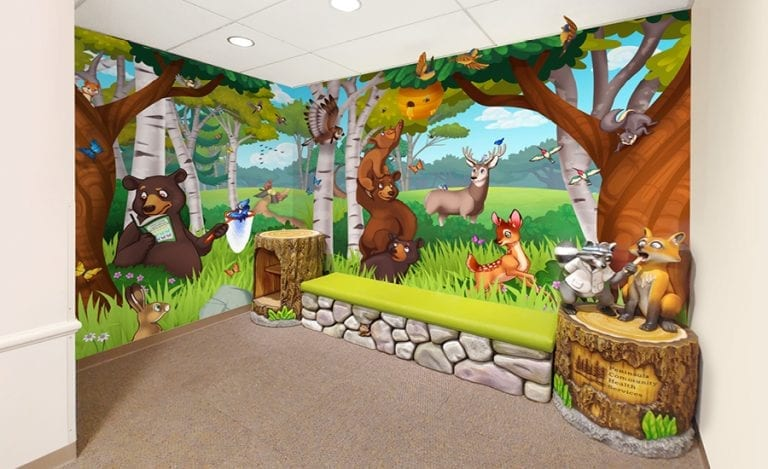 Forest themed quiet area with bench and bookshelf for kids.