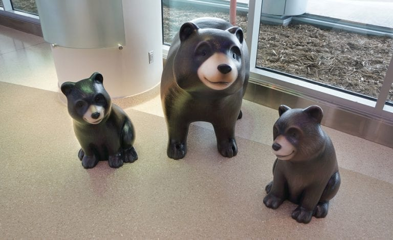 sculpted mama bear standing with two baby bear cubs that are sitting around her