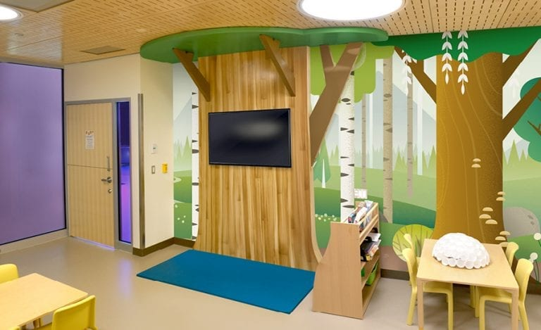 summery woodland mural with 3D cutout tree in a daycare room
