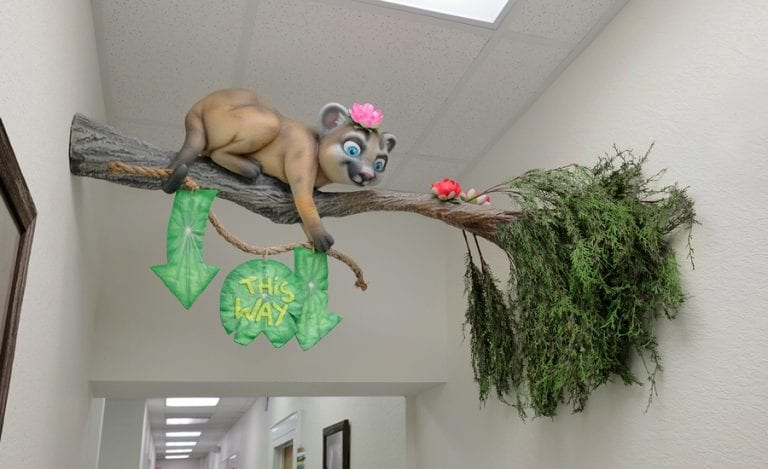 """sculpted cat laying on a tree branch holding wayfinding signage that says """"this way"""" on a Lilly pad"""