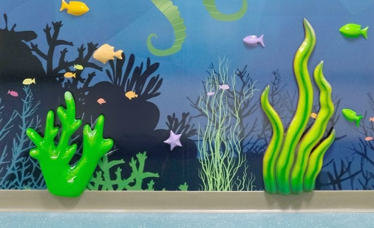 underwater themed wall mural with sculpted seaweed and coral for a childrens' hospital
