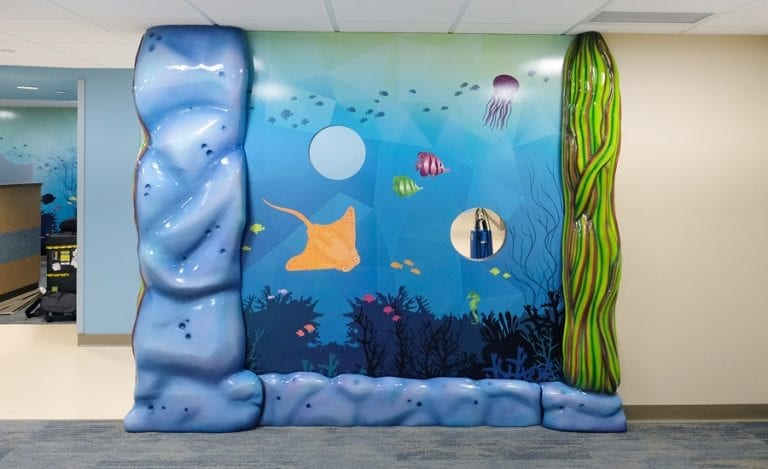underwater mural with sculpted rock and seaweed pillars for children's hospital