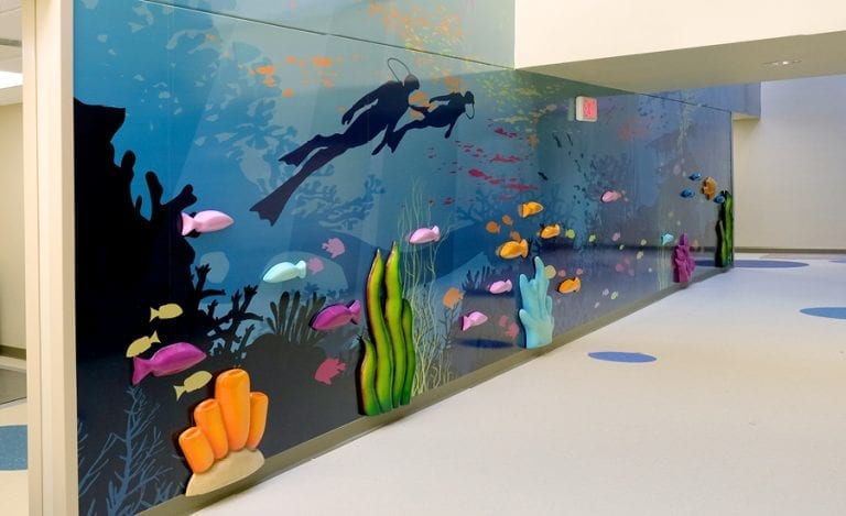 underwater themed wall mural with 3D sculpted coral and kelp
