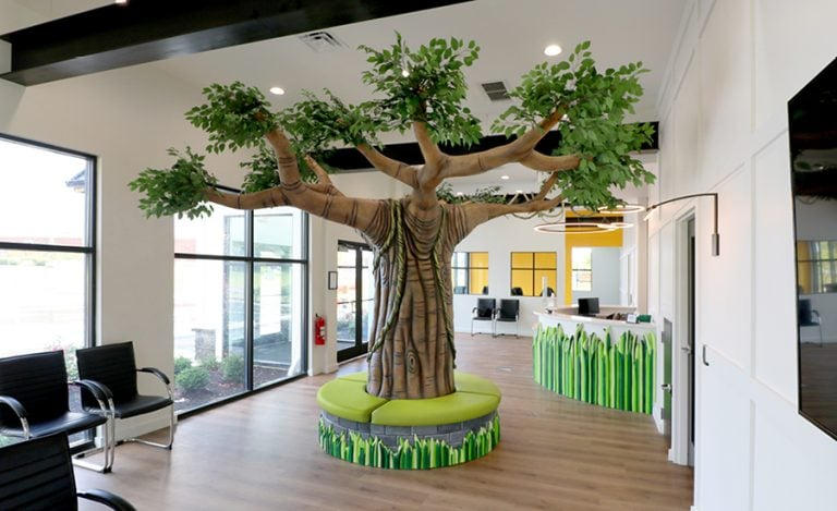 A tall tree centerpiece bench with comfy seating.