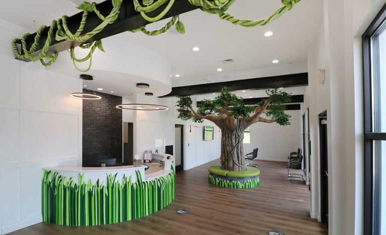 A modern jungle reception area with a grassy desk facade and tree bench centerpiece.