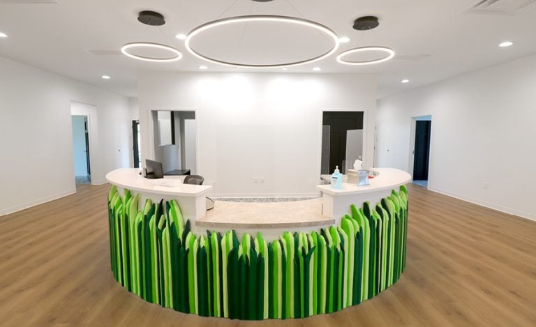 A contemporary themed reception desk covered in sculpted grass.